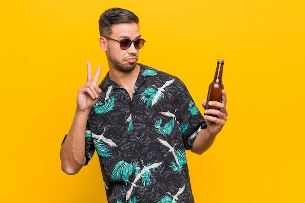 Giovane viaggiatore dell'asia del sud che tiene una bottiglia di birra.