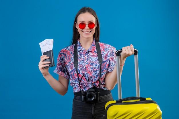 Giovane viaggiatore donna che indossa occhiali da sole rossi in piedi con la valigia gialla tenendo il passaporto e biglietti sorridendo allegramente guardando la fotocamera con la faccia felice su sfondo blu