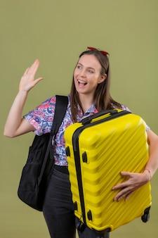 Giovane viaggiatore donna che indossa occhiali da sole rossi sulla testa in piedi con lo zaino che tiene la valigia agitando la mano mentre saluta o fa il gesto di addio sorridente con la faccia felice sul verde isolato