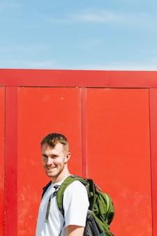 Giovane viaggiatore maschio felice con lo zaino di viaggio che esamina macchina fotografica
