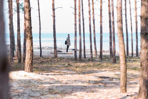 Giovane viaggiatore maschio in piedi vicino alla spiaggia