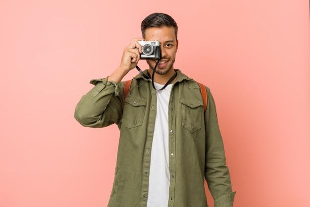 Giovane viaggiatore sud-asiatico che scatta foto con una fotocamera retrò.
