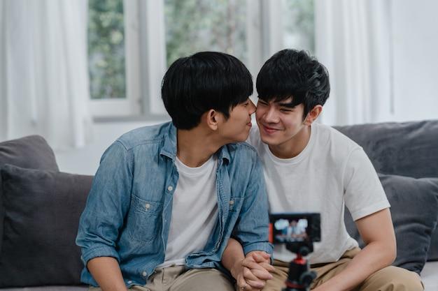 Giovane vlog gay asiatico delle coppie dell'influencer delle coppie a casa. gli uomini adolescenti coreani lgbtq si rilassano felici usando il caricamento del video del vlog del record della macchina fotografica nei social media mentre si trovano il sofà nel salone a casa.