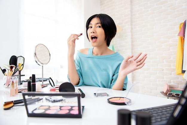 Giovane vlogger asiatico di bellezza della donna che fa esercitazione di trucco che trasmette online