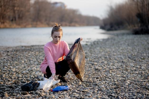 Giovane volontaria femminile che raccoglie immondizia sul fiume
