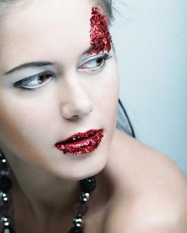 Giovane volto femminile con il trucco multicolore di moda brillante