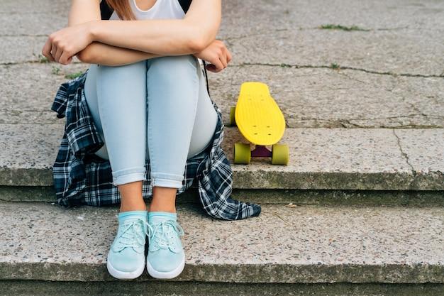 Giovane woaman in jeans, scarpe da ginnastica e t-shirt seduto sui gradini accanto al suo giallo skateboard all'aperto