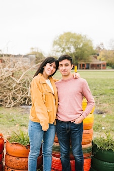 Giovani accoppiamenti positivi che stringono a sé nel parco di autunno