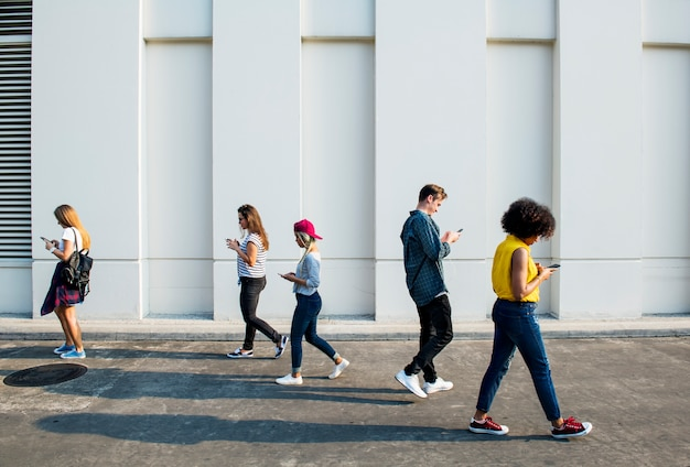 Giovani adulti che utilizzano gli smartphone mentre camminano all'aperto