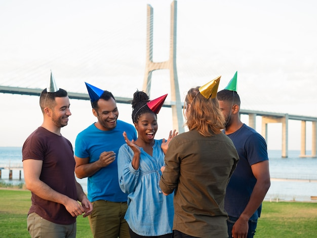 Giovani allegri che danno presente per la ragazza sorpresa. amici sorridenti che si congratulano giovane donna con il compleanno. concetto di festa di compleanno