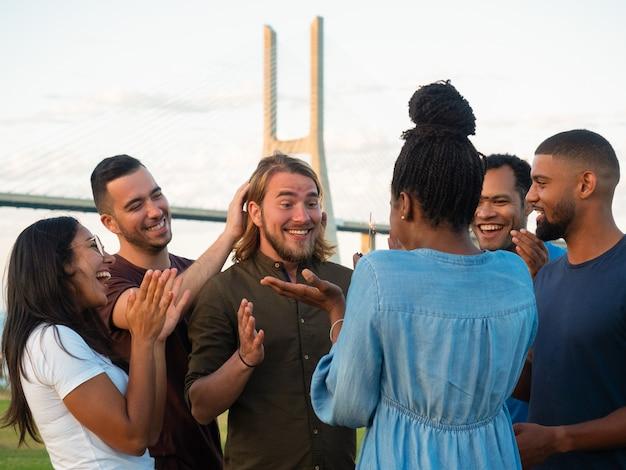 Giovani allegri che fanno sorpresa per l'amico maschio. donna afroamericana che presenta il muffin al cioccolato con la stella filante. concetto di sorpresa
