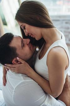 Giovani amanti uomo e donna in camera da letto sul letto.