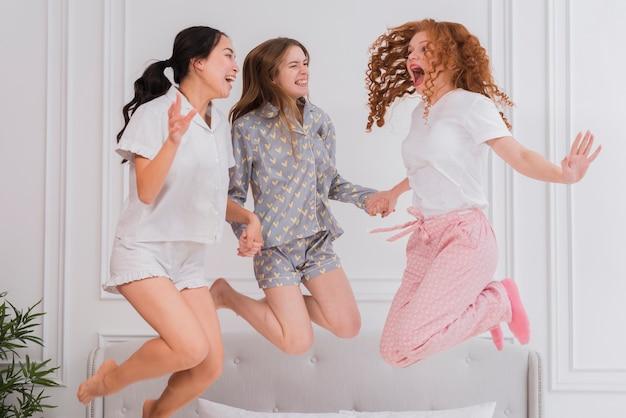 Giovani amiche che saltano nel letto
