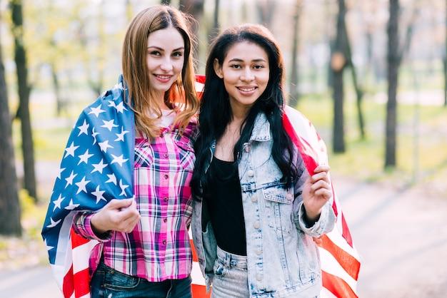 Giovani amiche che si spostano nella bandiera americana in piedi fuori