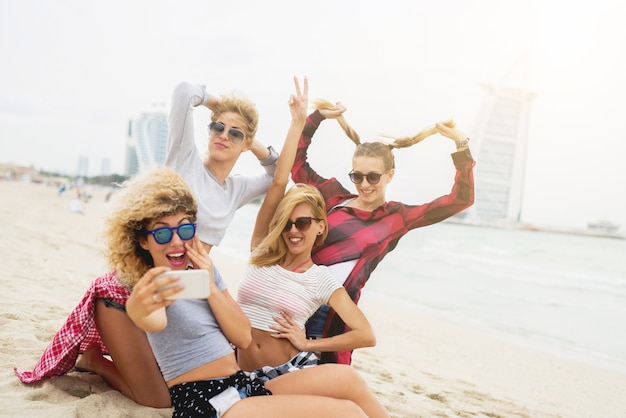 Giovani amiche sexy divertendosi e prendendo selfie sulla spiaggia. divertimento estivo da ragazza.