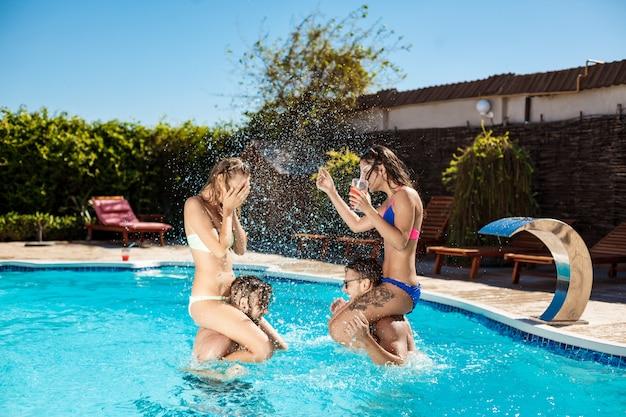 Giovani amici allegri che sorridono, che ridono, che si rilassano, che nuotano nello stagno