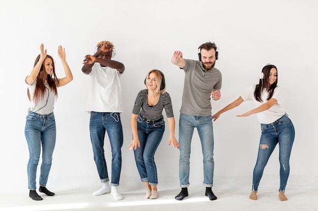 Giovani amici ascoltando musica e ballando