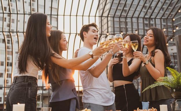 Giovani amici asiatici felici fanno festa ballando con la birra