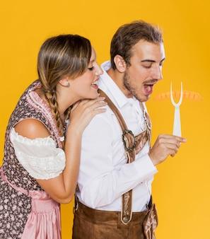 Giovani amici bavaresi con forchetta griglia