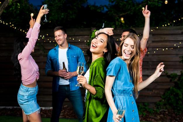 Giovani amici che ballano insieme all'aperto