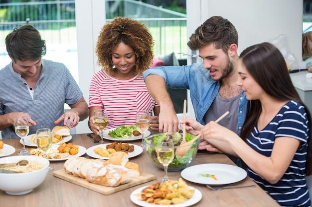 Giovani amici che hanno un pasto al tavolo