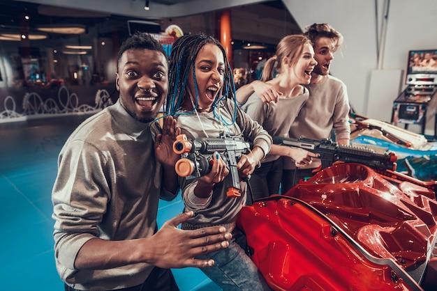 Giovani amici che posano con pistole nere in sala giochi.