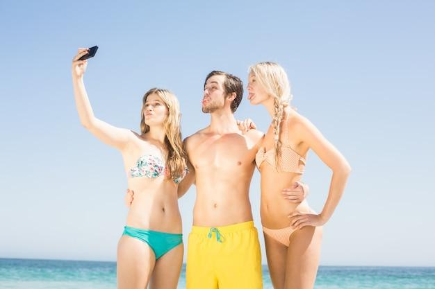 Giovani amici che prendono un selfie sulla spiaggia