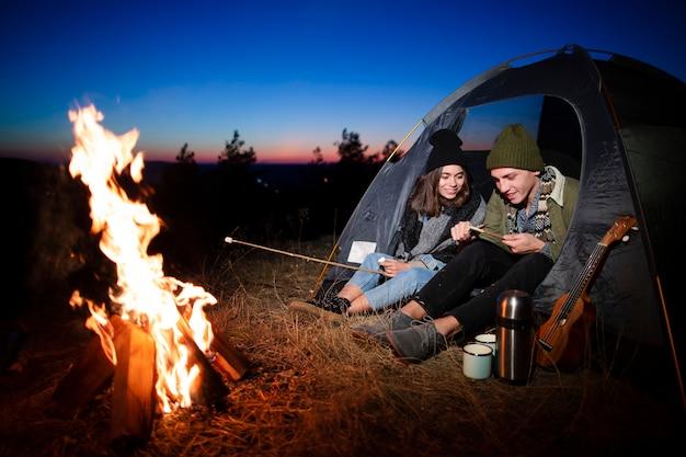 Giovani amici che preparano marshmallow