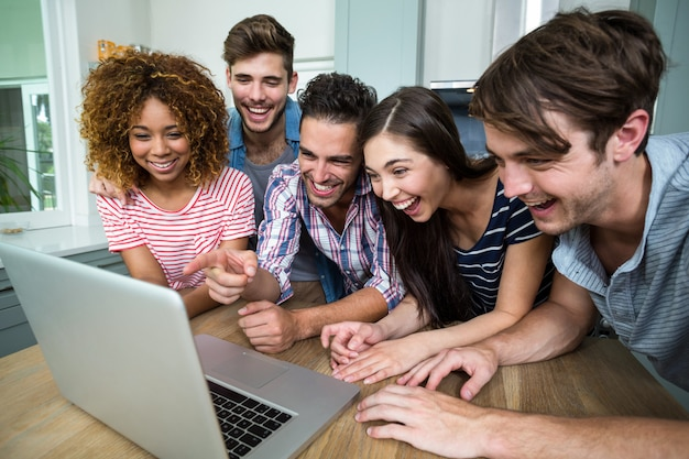 Giovani amici che ridono mentre osservano in computer portatile sulla tabella