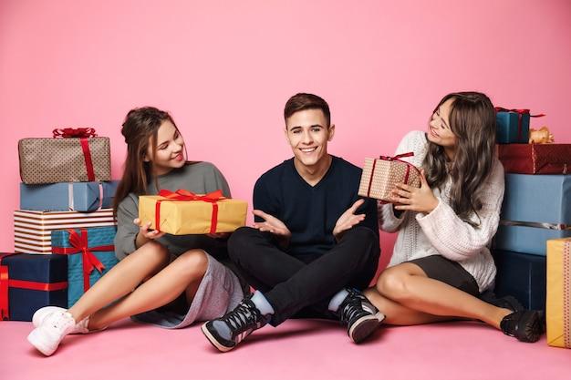 Giovani amici che si siedono fra i contenitori di regalo di natale sul rosa