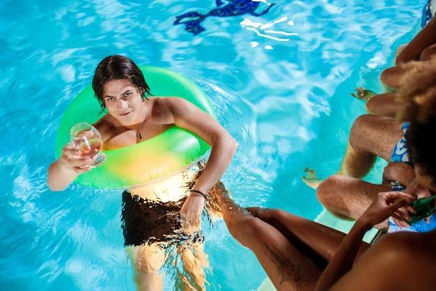 Giovani amici che sorridono, rallegrandosi, riposando alla festa vicino alla piscina