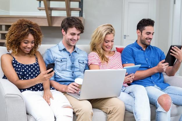 Giovani amici che usano le tecnologie mentre sono seduti sul divano