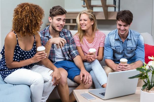 Giovani amici con bevande seduti sul divano