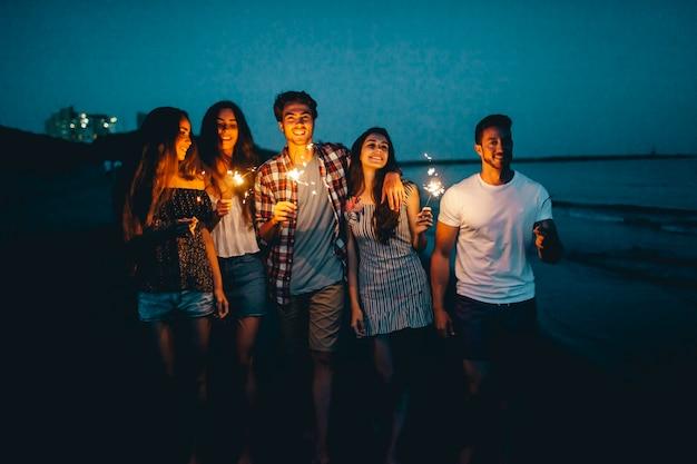 Giovani amici con sparklers in una spiaggia notturna