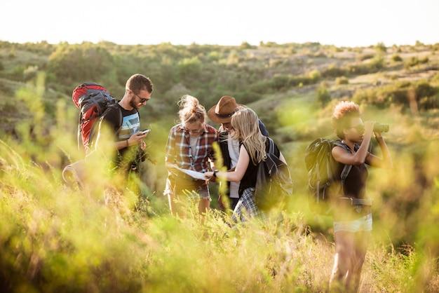 Giovani amici con zaini che godono della vista, viaggiando nel canyon