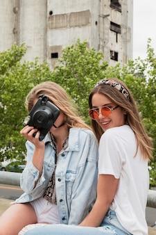Giovani amici dell'angolo alto in città che prendono le foto