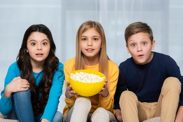 Giovani amici di angolo basso che guardano film