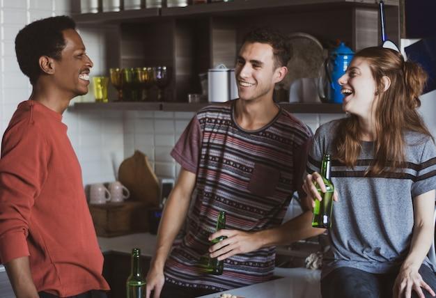 Giovani amici divertendosi con le bottiglie a casa.