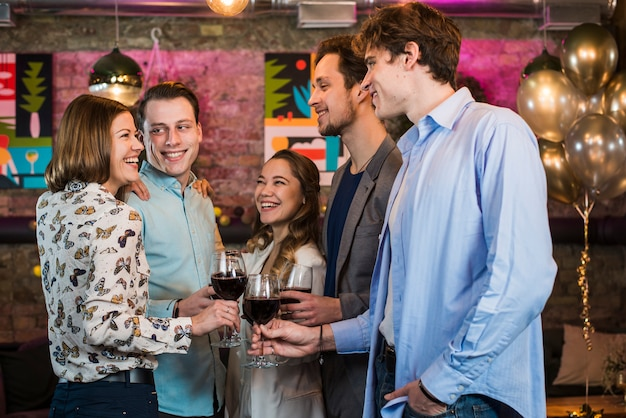 Giovani amici felici che celebrano e che tostano vino in barra