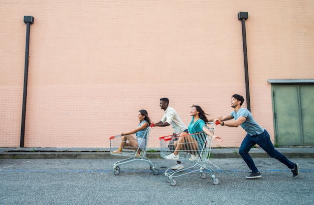 Giovani amici felici che corrono con i carrelli