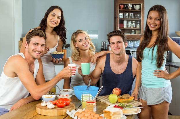 Giovani amici felici che mangiano prima colazione a casa
