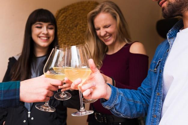 Giovani amici felici che tengono vetro di alcool a disposizione