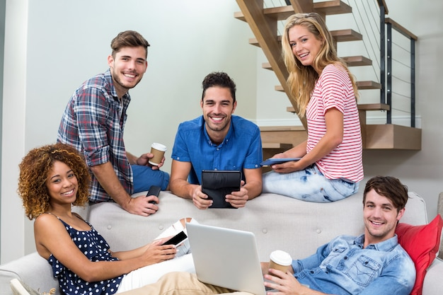 Giovani amici felici che usando le tecnologie moderne sul sofà