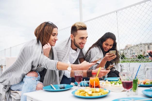 Giovani amici felici erano seduti a un tavolo e facevano un picnic all'aperto.