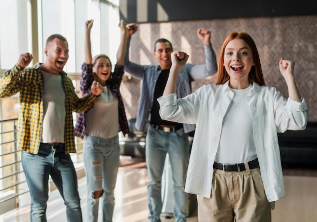 Giovani amici felici in piedi in un club di bowling