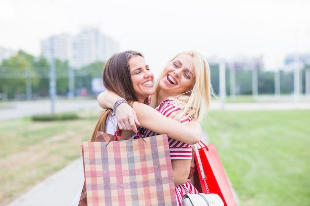 Giovani amici femminili che si abbracciano tenendo le borse della spesa
