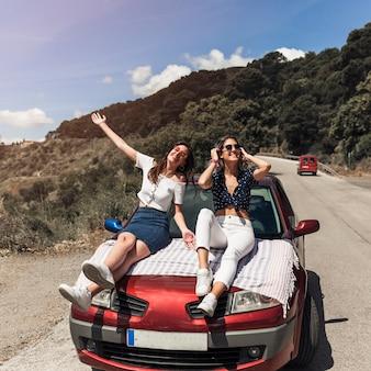 Giovani amici femminili che si siedono sopra il cappuccio dell'automobile che fa divertimento sulla strada