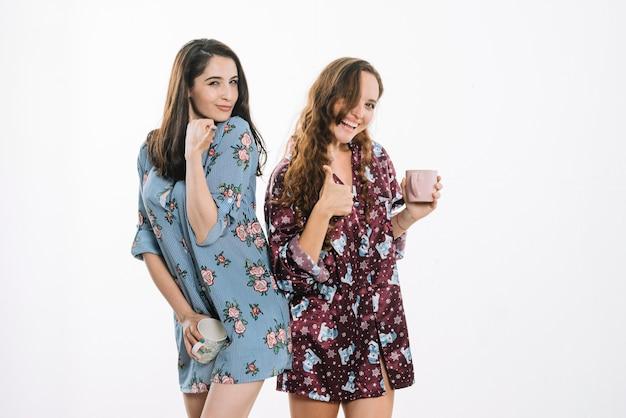 Giovani amici femminili con la tazza di caffè che gesturing i pollici su