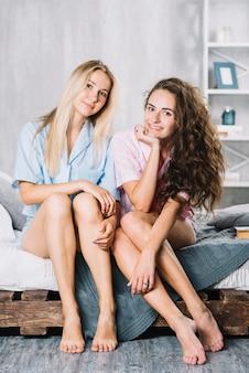 Giovani amici femminili sorridenti che si siedono sul letto a casa