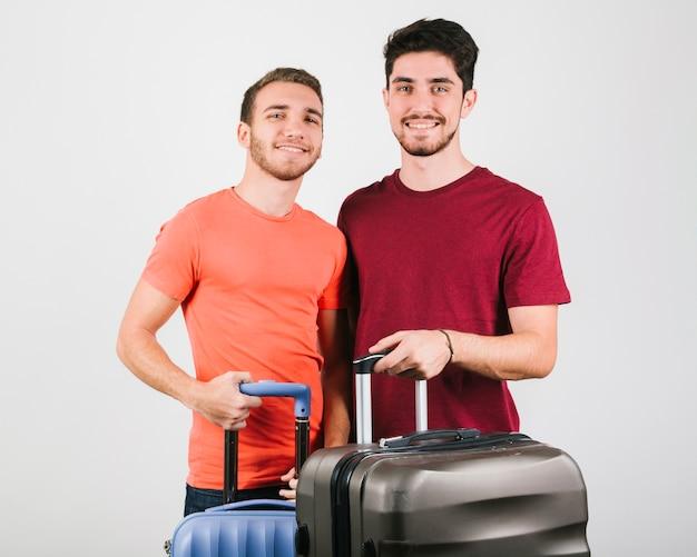 Giovani amici in magliette luminose in piedi con le valigie
